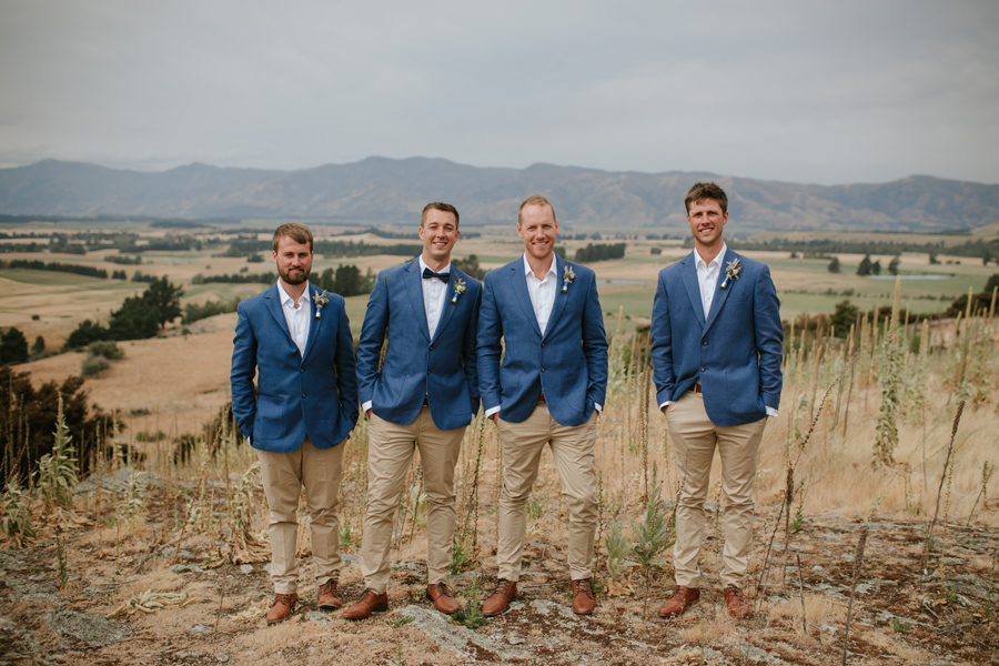 A groom and his 3 groomsmen in blue suit jackets stand on a hill with mountains behind them. Photography by Alpine Image Company.