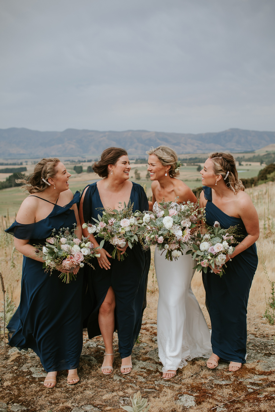 A bride and her beautiful maids stand laughing with hills behind them. They carry floral bouquets. Photography by Alpine Image Company