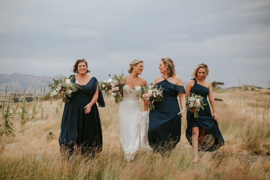 A bride and her 3 bridesmaids walk in long grass smiling on their wanaka wedding day. Photography by Alpine Image Company.