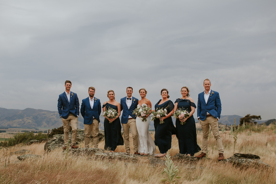 A bridal party stand on rocks in a field of long grass with hills behind them. Photography by Alpine Image Company