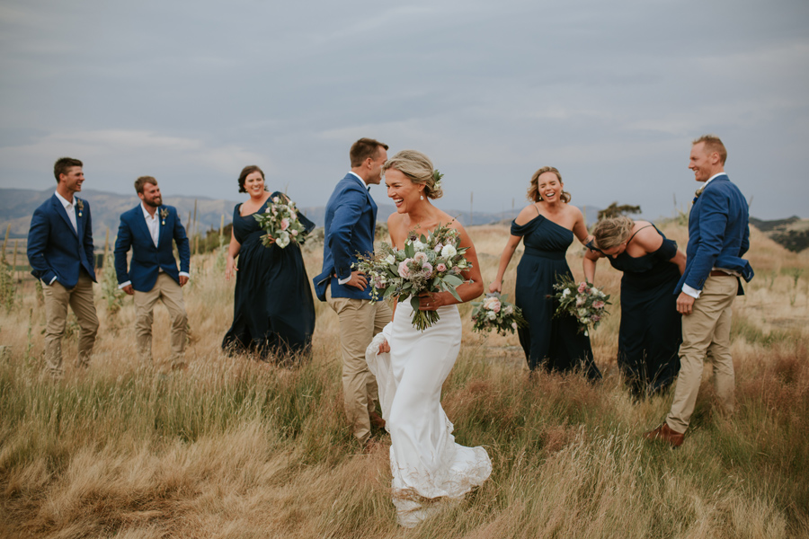 A bridal party all laugh at at bridesmaid who has fallen over whilst walking in a field of long grass in Wanaka. Photography by Alpine Image Company.