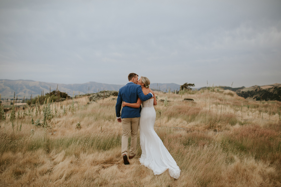 A bride and groom kiss whilst walking in long grass in Wanaka. the sky is cloudy and moody. Photography by Alpine Image Company.
