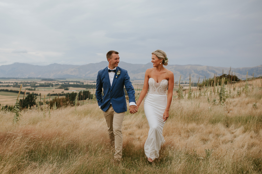 A bride and groom walk smiling hand in hand through a field of long grass. There are mountains behind them. Photography by Alpine Image company.
