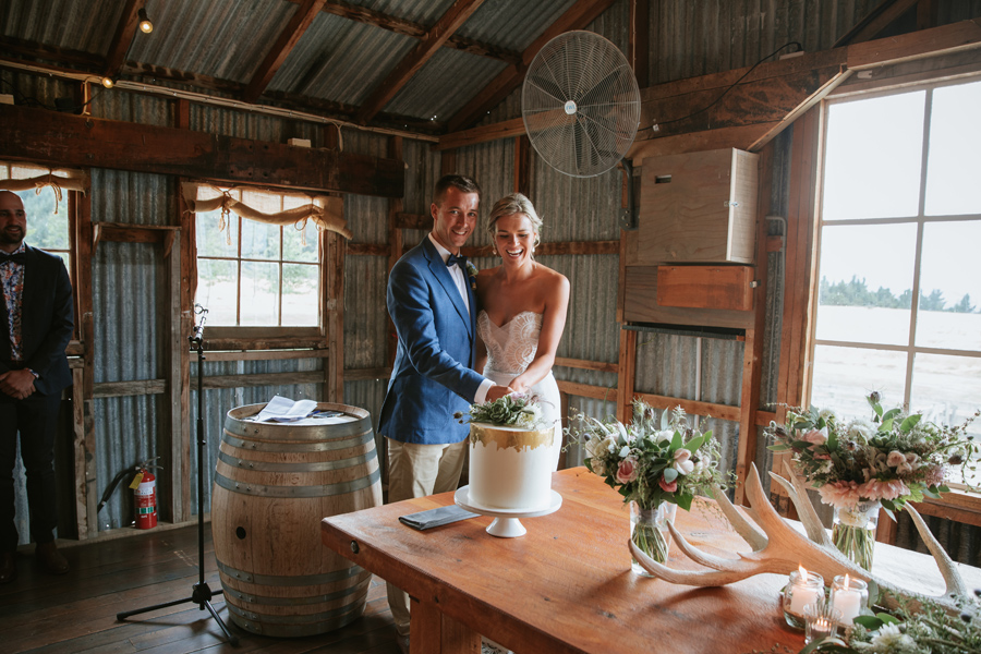 A bride and groom cut their white wedding cake which is on a wooden table inside a woolshed in Wanaka. Photography by Alpine Image Company.