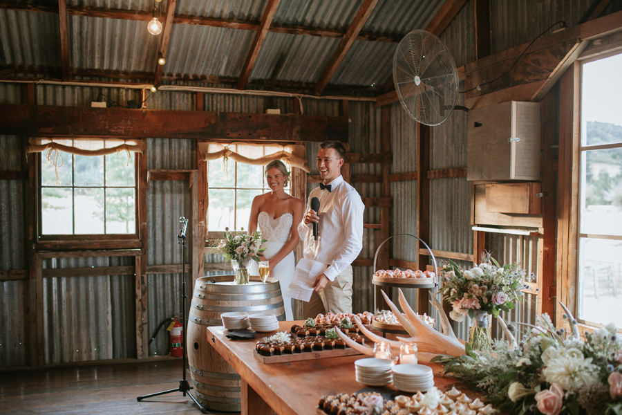 A bride and groom give their wedding day speech standing behind a wine barrel in a woolshed. Photography by Alpine Image Company.