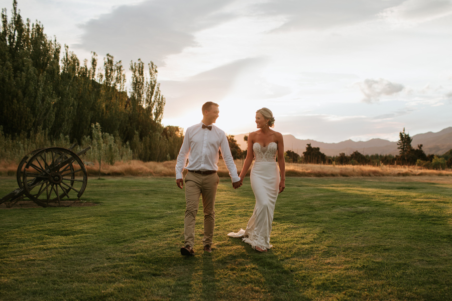 at golden hour a happy couple walk hand in hand in green grass with the setting sun behind them. Photography by Alpine Image Company.