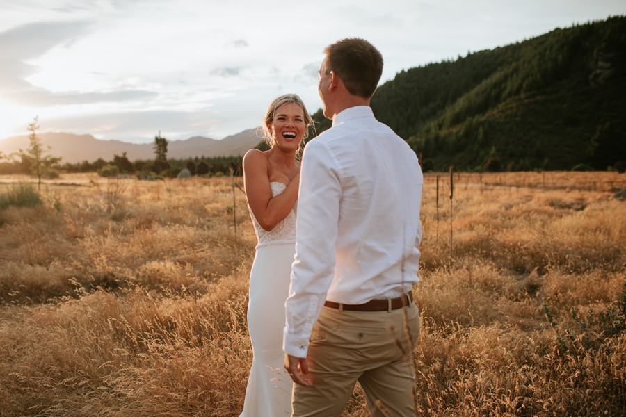 A bride laughs facing her groom in a field of long golden grass with the sun behind them. Photography by Alpine Image Company.
