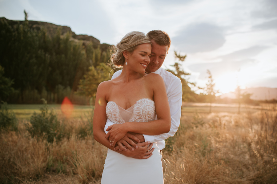 A bride and groom spoon in a field of golden grass with the sun setting. Photography by alpine Image company.