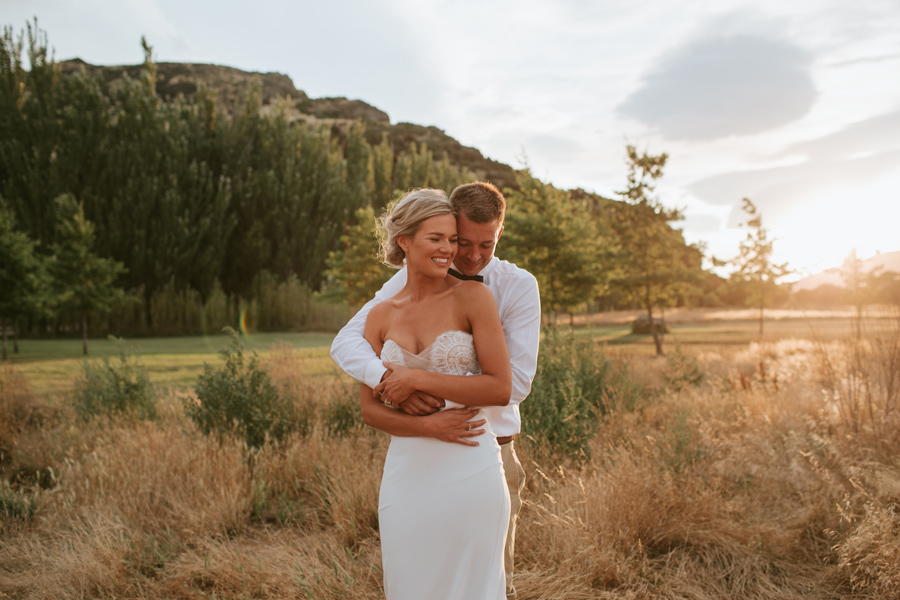 A groom cuddles his bride from behind whilst the golden sunlight is just above the hill behind them. Photography by alpine Image company