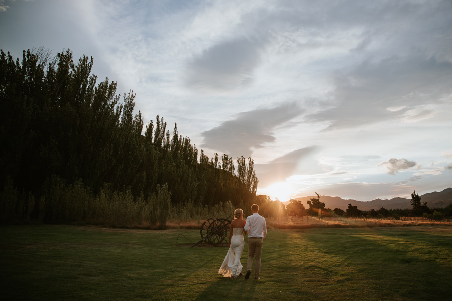 Walking hand in hand towards a wooden cart, a happy couple walk towards the setting sun in Wanaka. Photography by Alpine Image Company.
