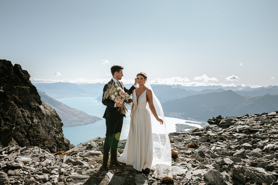 A groom touches his brides face as they stand on a mountain top on their Queenstown elopement wedding day. There is a blue lake in the distance and mountains in the background. The sky is blue. With photography by Alpine Image Company