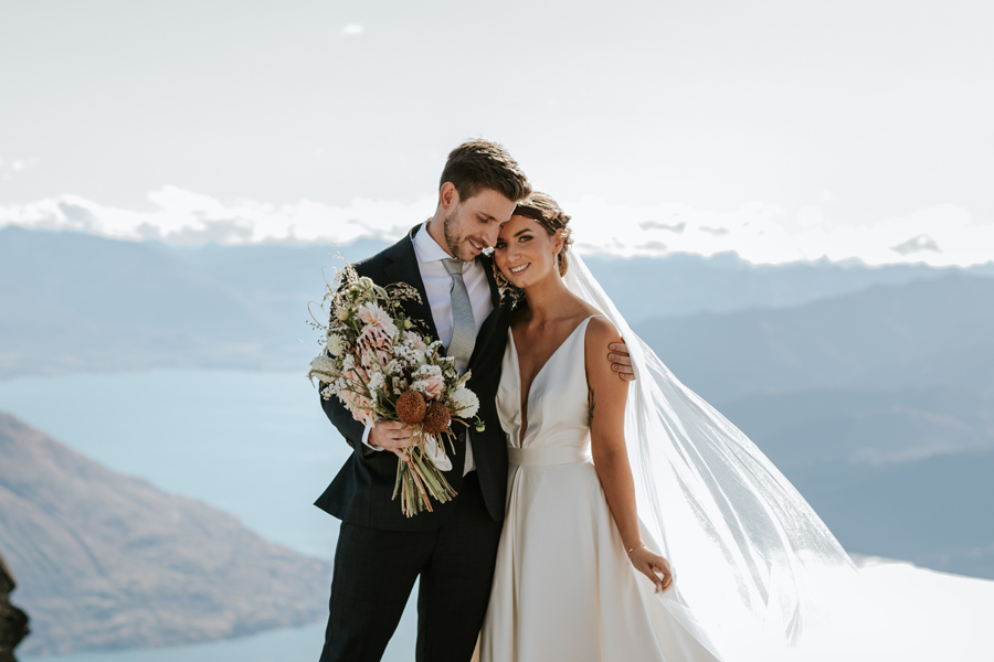 A couple embrace on their Queenstown Wedding day. They are standing on a mountain top with a blue lake and mountains in the distance. With photography by Alpine Image Company