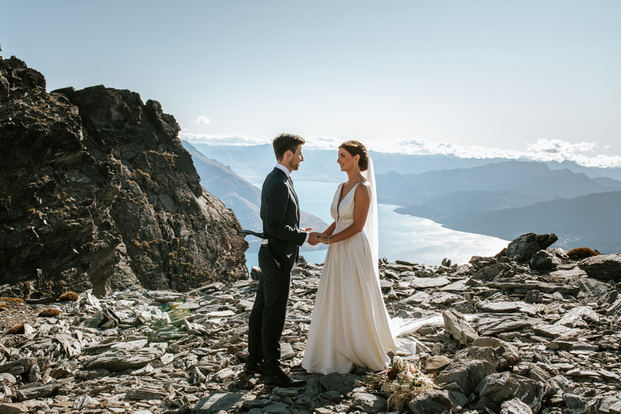 A couple on their Queenstown Elopement Wedding hold hands and look towards each other. They are standing on a mountain top and there is a blue lake and mountains in the distance. With photography by Alpine Image Company