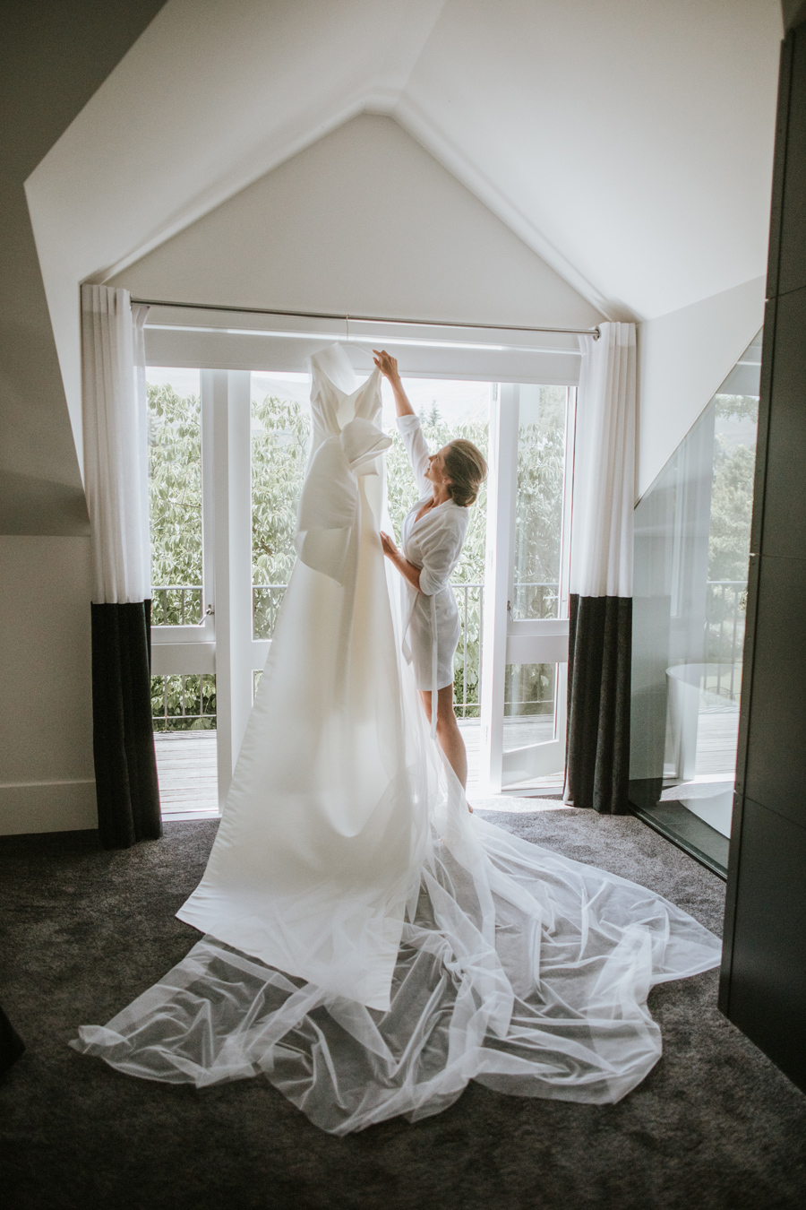 A bride reaches for her wedding gown on her Queenstown Wedding day. With photography by Alpine Image Company