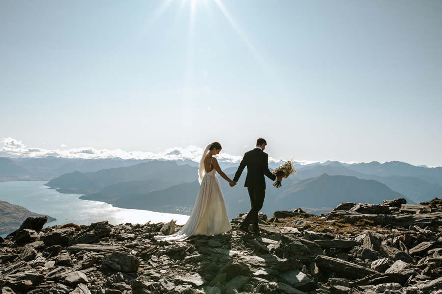 A bride and groom walk along a ridgeline on their Queenstown Wedding day. There is a lake in the distance and mountains surround them. With photography by Alpine Image Company