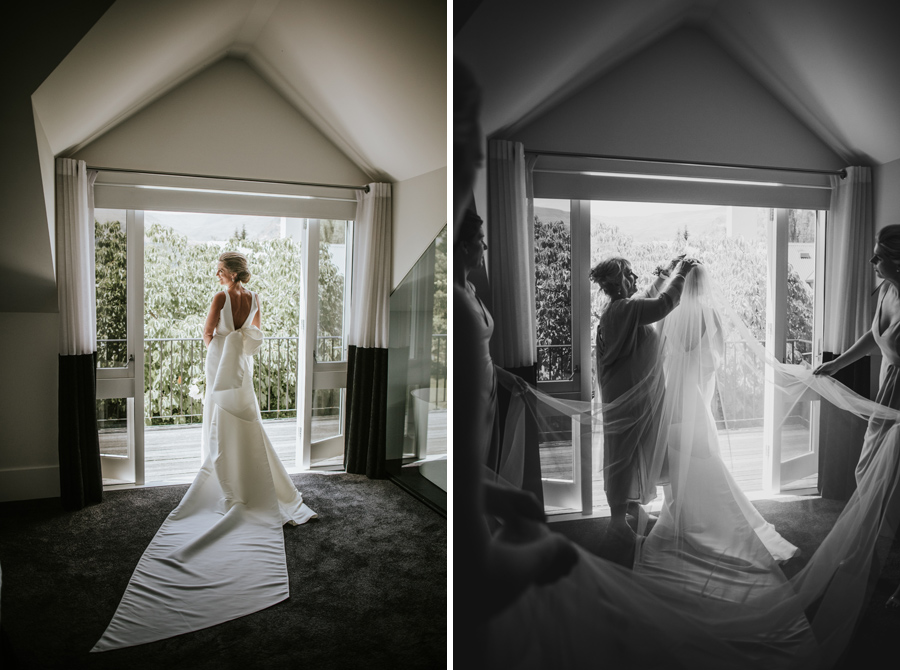 A bride stands in the window in her Trish Peng wedding gown on her Queenstown Wedding Day. With photography by Alpine Image Company
