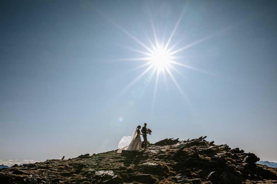 A bride and groom on their Queenstown Elopement Wedding, walk along a ridge line. There is a sunburst in the sky behind them and the sky is blue. With photography by Alpine Image Company