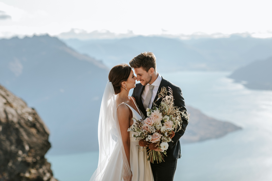 A couple share an intimate moment with their heads together on their Queenstown Elopement Wedding day. There is a blue lake behind them and mountains in the backgronud. With photography by Alpine Image Company