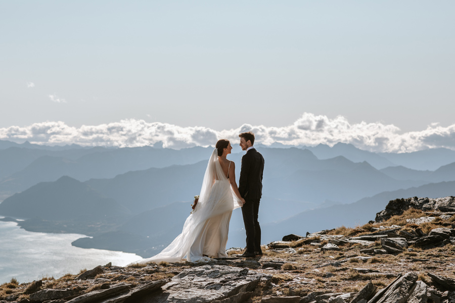 A bride and groom hold hands on a mountain top on their Queenstown Wedding day. There is a lake in the distance and mountains in the background. With photography by Alpine Image Company
