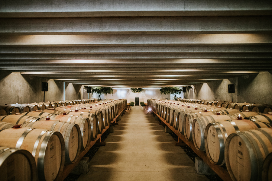 A wedding set up at Peregrine Winery near Queenstown. Barrels of peregrine wine line the brides entrance. With photography by Alpine Image Company