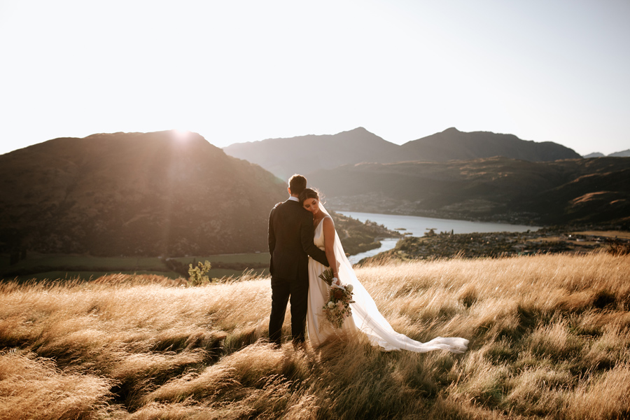 A bride rests her head on her grooms shoulder on their Queenstown Elopement Wedding day. The sun is setting behind them and they stand in a field of golden grass. With photography by Alpine Image Company