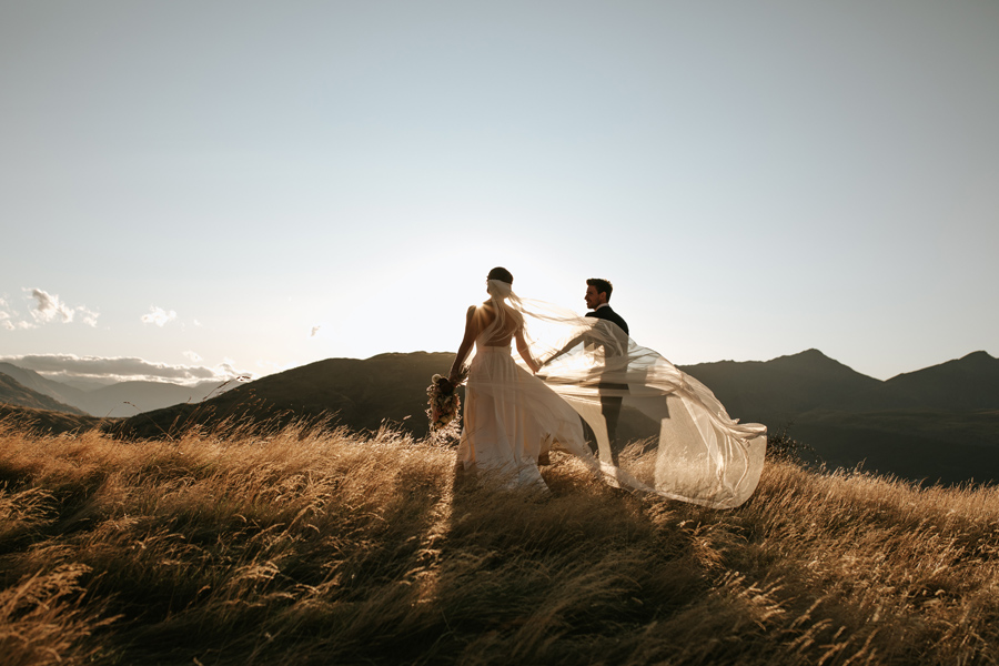 A bride and groom walk through a field of golden grass as the sun sets on their Queenstown Wedding Day. With photography by Alpine Image Company