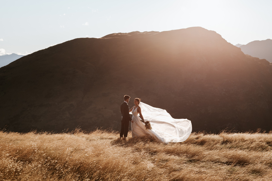 On their Queenstown Elopement Wedding day, a bride and groom stand in a field of golden grass. The bride holds out her veil. There are mountains in the distance. With photography by Alpine Image Company