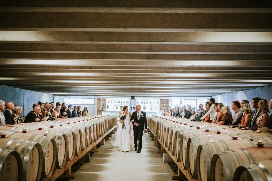 A birde walks down the aisle on her Queenstown Wedding Day at Peregrine Winery. With photography by Alpine Image Company