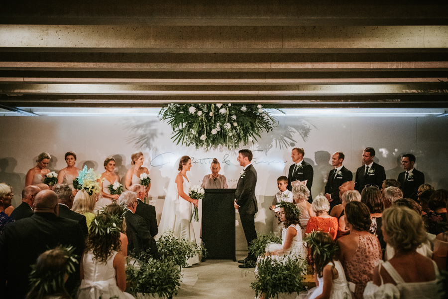 A bride and groom smile at each other during their ceremony on their Queenstown Wedding Day. They are being married in the wine cellar of Peregrine Winery. With photography by Alpine Image Company