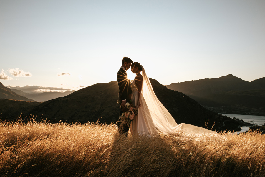 A bride and groom stand with their heads together, on their Queenstown Elopement Wedding day. There are sillouetted mountains in the distance behind them, and a sunburst between them. The grass is golden. With photography by Alpine Image Company