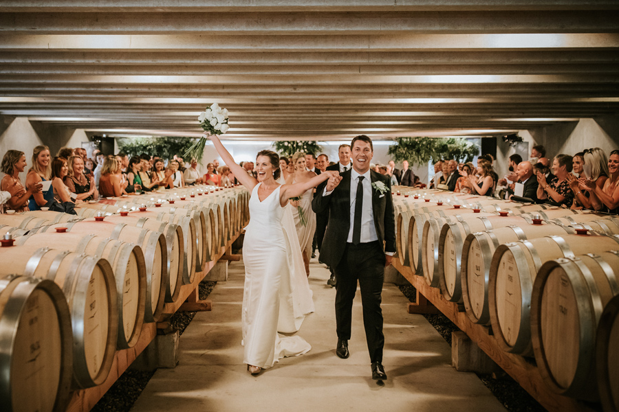 A bride and groom celebrate as they walk down the aisle on their Queenstown Wedding Day. They walk in between rows of wine barrels. Their ceremony was held at Peregrine Winery. With photography by Alpine Image Company