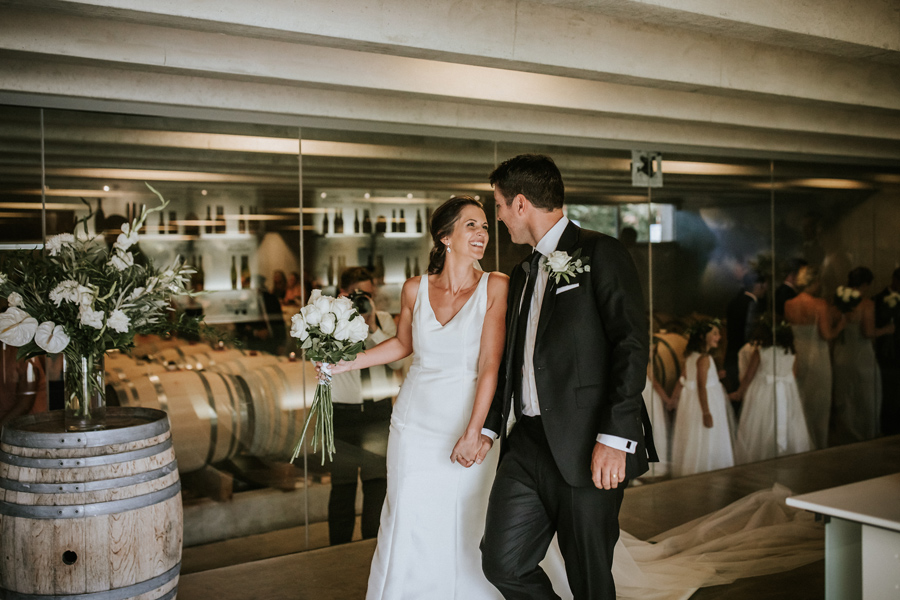 A newly married couple smile at each other as they leave the wine cellar of Peregrine Winery, where they held their wedding ceremony. With photography by Alpine Image Company