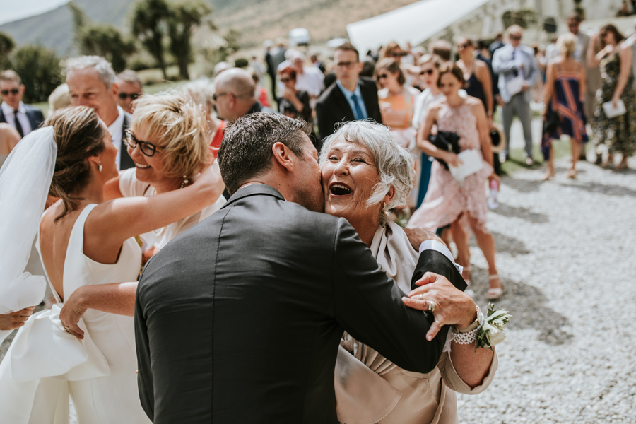 A groom kisses his delighted mother on the cheek in celebration, on his Queenstown Wedding Day. The mum smiles and there are guests in the background waiting to congratulate the couples. With photography by Alpine Image Company