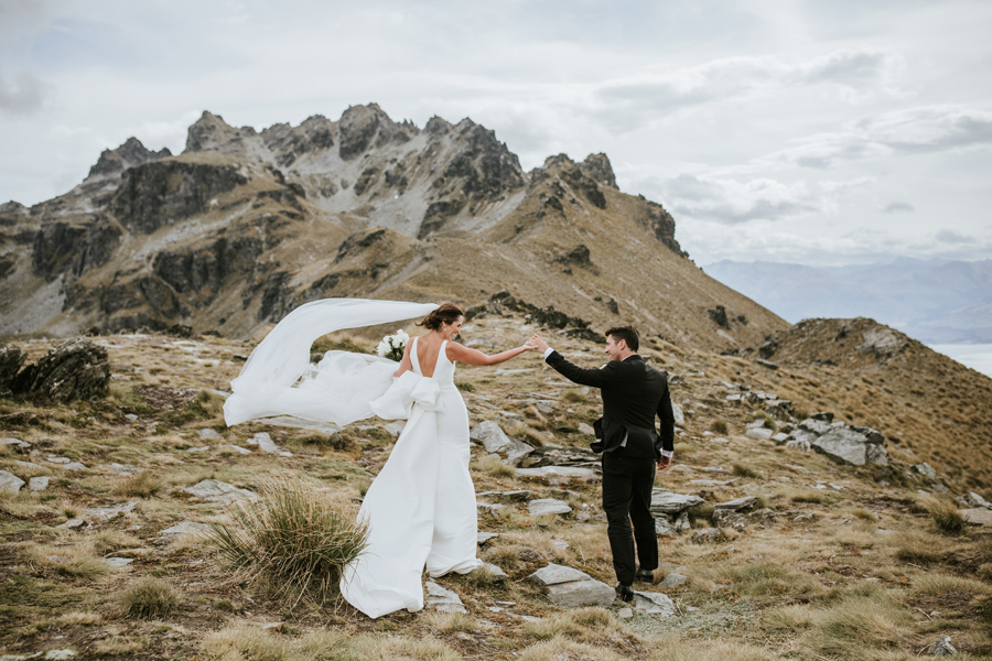A bride and groom walk hand in hand away from the camera, in the Queenstown Mountains on their Queenstown Wedding Day. There is a large mountain behind them and high cloud in the sky. With photography by Alpine Image Company