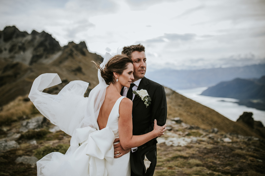 A bride and groom embrace on their Queenstown Wedding Day. There is a lake behind them and jagged mountain peaks. With photography by Alpine Image Company