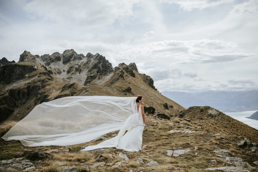 A bride in her Trish Peng Wedding Dress stands in the Queenstown Mountains on her Queenstown Wedding day. With photography by Alpine Image Company