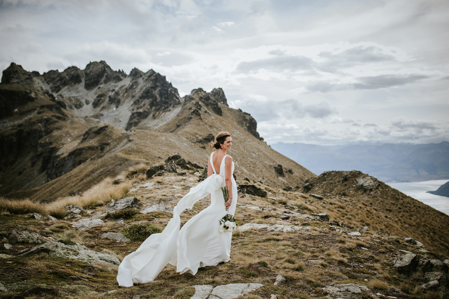 A bride stands smiling in her Trish Peng wedding dress. She is standing on Cecil Peak, a mountain near Queenstown on her Queenstown wedding day. There are jagged mountain peaks in the background and a blue lake in the distance. The sky is cloudy and the wind is blowing her dress. With photography by Alpine Image Company