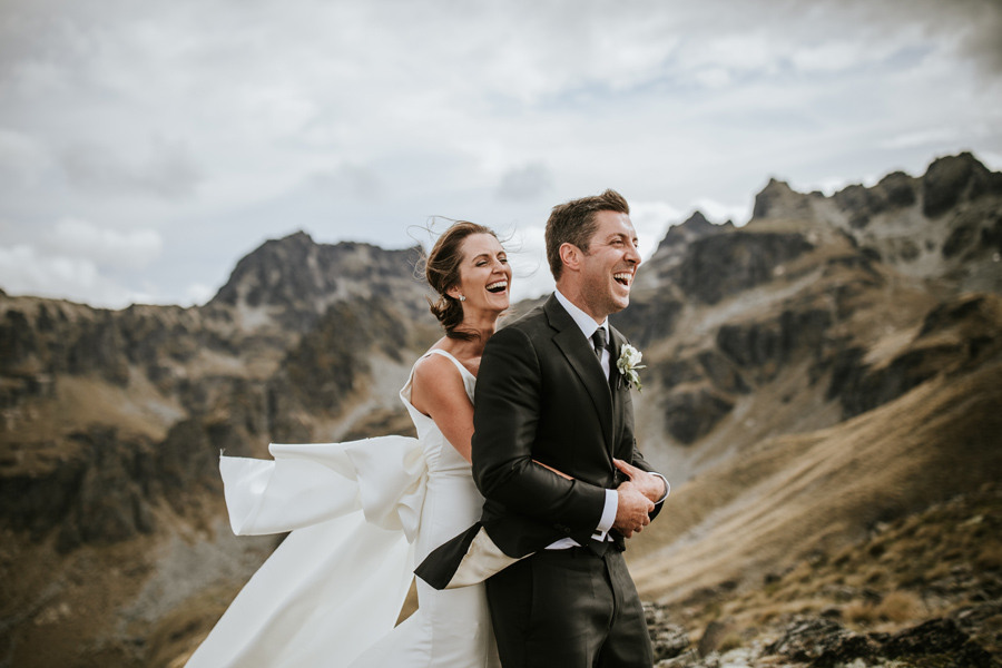 A bride and groom laugh together on their Queenstown wedding day. They are standing on a mountain peak with jagged rocks in the background. With photography by Alpine Image Company