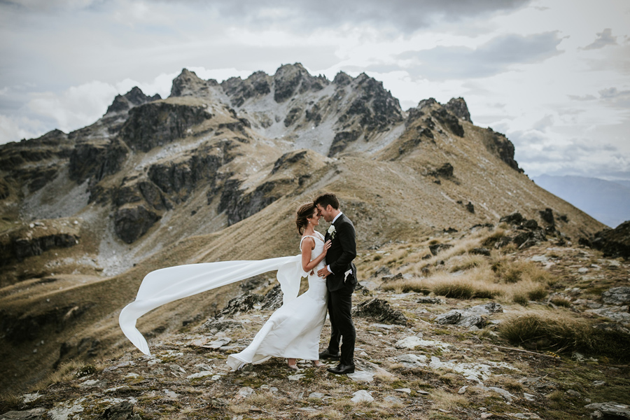 A bride and groom stand with their heads together in front of Cecil Peak, on their Queenstown Wedding Day. The rocks behind them are jagged and look beautiful. With photography by Alpine Image Company