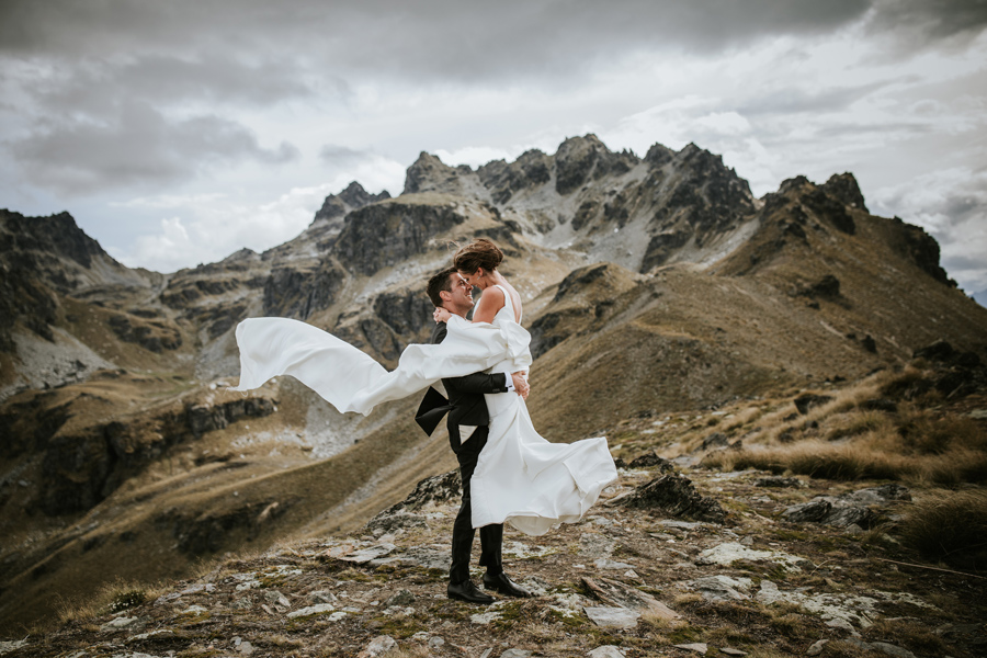 A groom lifts his bride and her trish peng wedding gown blows in the wind. They are standing on a mountain top with jagged rocks in the background. The sky is cloudy and the weather looks windy. With photography by Alpine Image Company