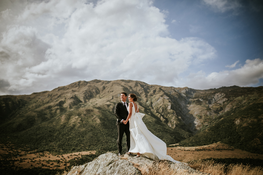 A bride and groom stand admiring the view at Peregrine Vineyard on their Queenstown wedding day. The sky above them is blue and there are mountains in the background. With photography by Alpine Image Company.