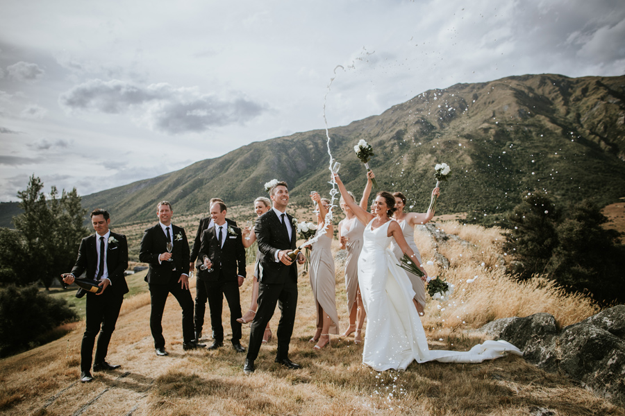 A bridal party celebrate a wedding at Peregrine Vineyard by popping a bottle of bubbles. They cheer as the bubbles spray in the air. The sky is cloudy and the mountains behind them are green with forest. With photography by Alpine Image Company.