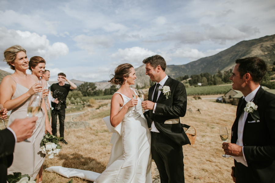 A couple cheers each other on their Queenstown Wedding Day. They are standing in a field at Peregrine Winery accompanied by their bridal party, and the sky behind them is blue. With photography by Alpine Image Company