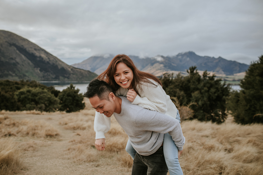 A man carries his girlfriend on his back in a field of long grass overlooking Lake Wanaka on their engagement shoot. Photography by Alpine Image Company