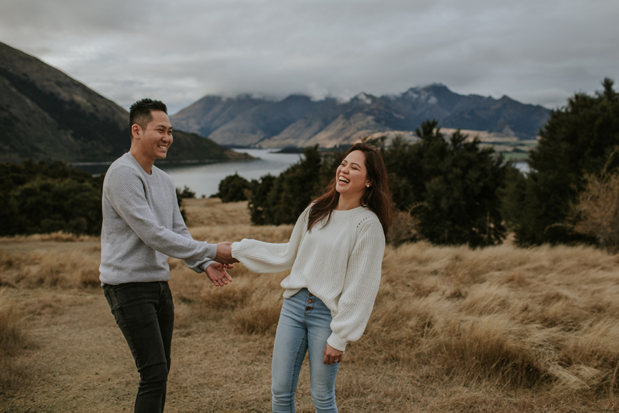 A couple laugh holding hands in a paddock overlooking Lake Wanaka. Photography by Alpine Image Company.