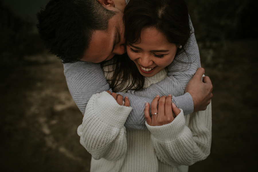 A laughing girl is being cuddled from behind by her boyfriend. They are dressed in casual clothes. Photography by Alpine Image Company.